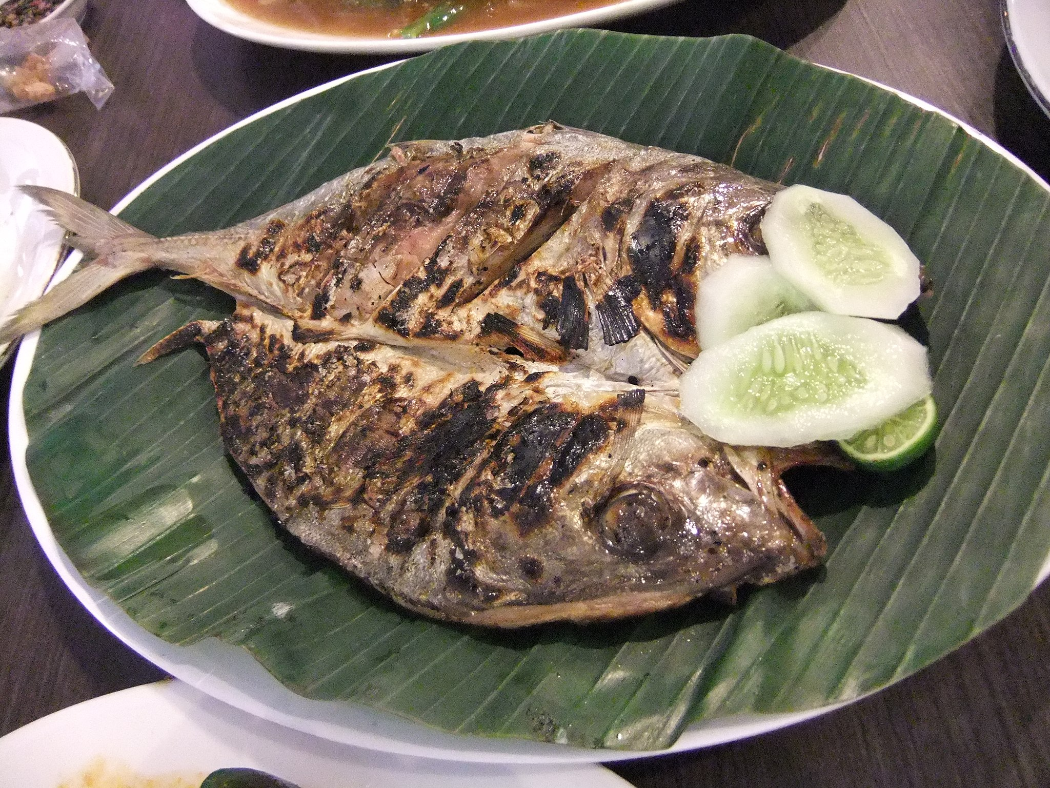 Grilled fish garnished with cucumber slices