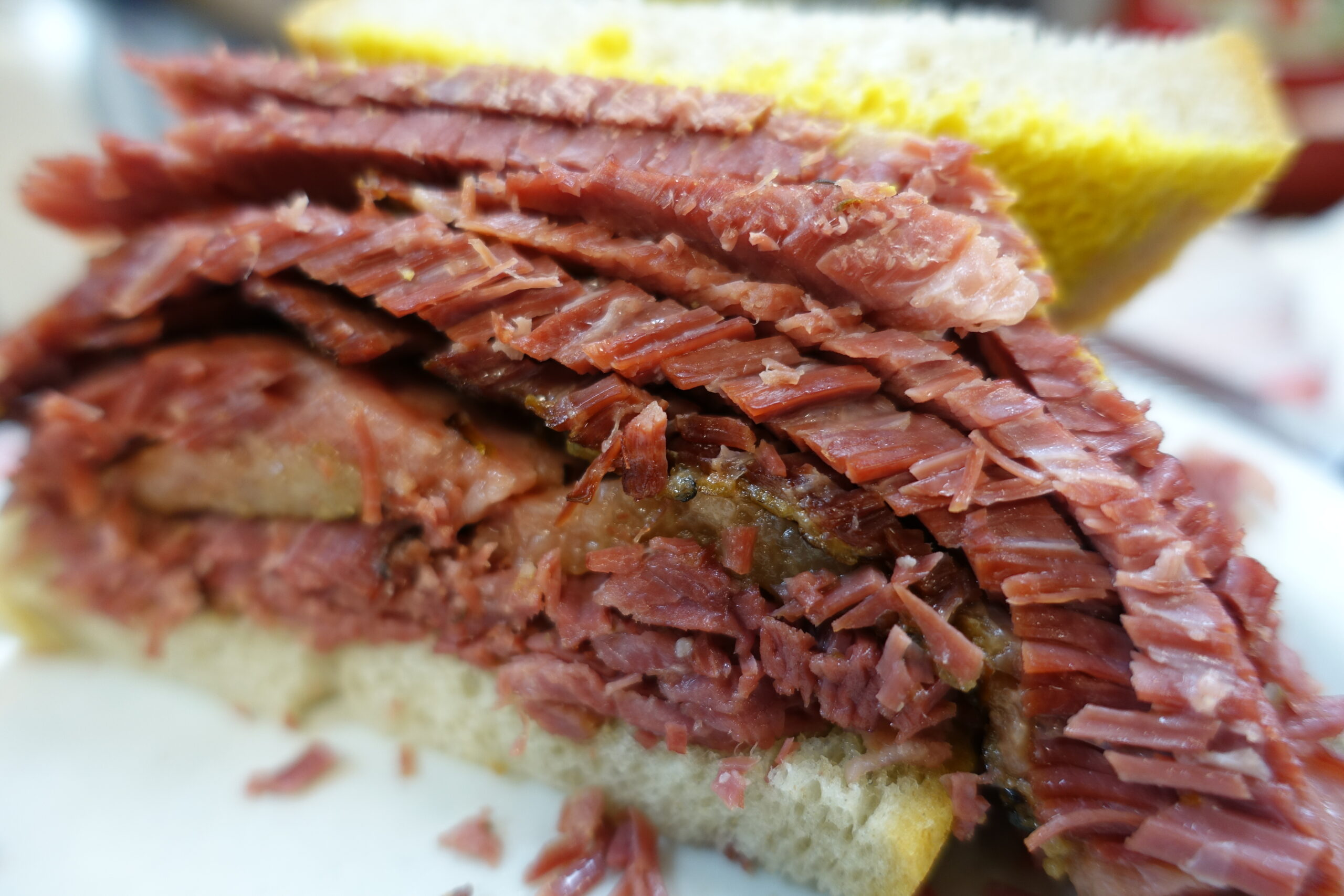 Delicious Destinations Montreal - A sandwich with smoked thinly cut cow belly and mustard