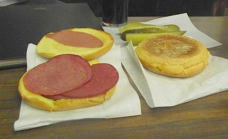 A sandwich with mustard, salami, bologna and pickles