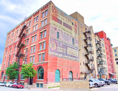 red brick building with old painted signs and fire escapes in the Exchange district of Winnipeg - photo by Dave Shaver under CC BY 2.0